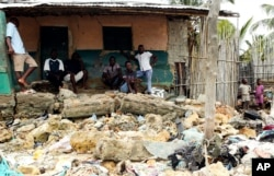 Community members look at rubble and other items washed close to their doorstep when Cyclone Kenneth struck in Pemba city on the northeastern coast of Mozambique, April, 27, 2019. Cyclone Kenneth arrived late Thursday, just six weeks after Cyclone Idai ripped into central Mozambique and killed more than 600 people.