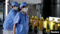 資料圖片:2018年7月4日,中國一工廠工人用美國大豆提煉生產瓶裝豆油。
