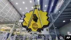 In this April 13, 2017 photo provided by NASA, technicians lift the mirror of the James Webb Space Telescope using a crane at the Goddard Space Flight Center in Greenbelt, Md. (Laura Betz/NASA via AP)