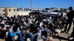 African illegal migrants wait to receive medial assistance after being rescued by coastal guards at a port in Tripoli, Libya, April 11, 2016.
