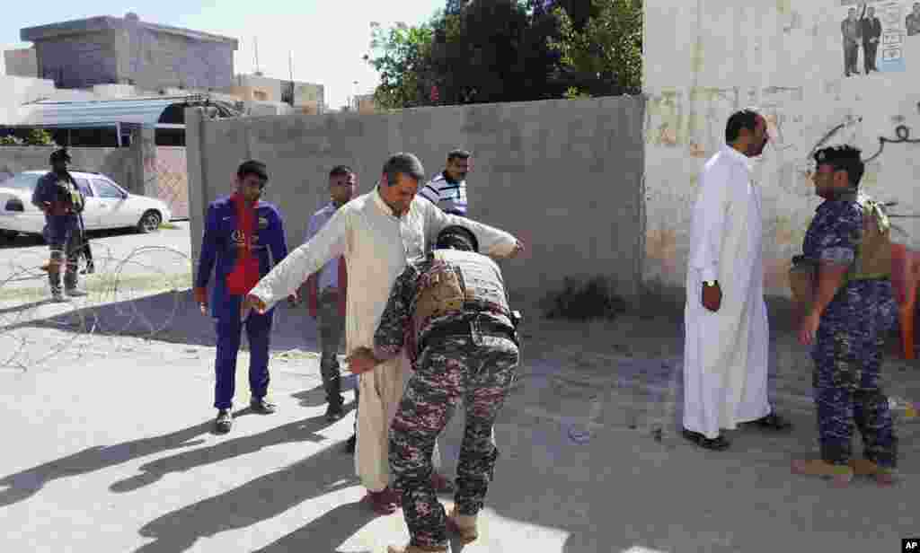 Security forces search people outside a polling station in Habaniyah, near Fallujah, April 30, 2014.