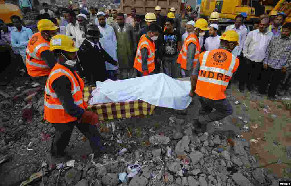 Rescue workers use a stretcher to carry the body of a victim across the rubble after the collapse of a residential building in Thane district, on the outskirts of Mumbai, April 6, 2013.
