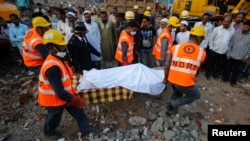 Rescue workers use a stretcher to carry the body of a victim across the rubble after the collapse of a residential building in Thane district, on the outskirts of Mumbai, Apr. 6, 2013.