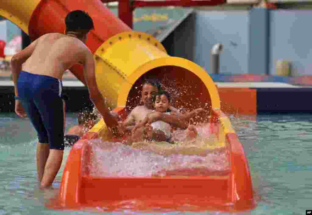 هوای ۴۸ درجه سانتیگرادی در عراق، مردم را وادار کرده به آب بزنند. تصویر از یک پارک آبی در بغداد است.