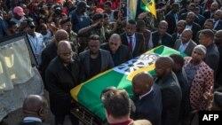 Quelques personnes portent le cercueil de Winnie Madikizela-Mandela recouvert d'un drapeau de l'ANC à Soweto, Johannesburg, le 13 avril 2018.