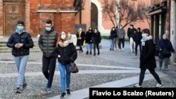 Orang-orang mengenakan masker berjalan-jalan di alun-alun Kota Codogno, Italia, satu tahun setelah kota itu menjadi pusat wabah pandemi COVID-19 di Eropa, 11 Februari 2021. (Foto: Flavio Lo Scalzo/Reuters)