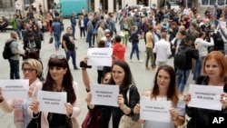 "Bosnian journalists hold up banners reading ""Journalism is not a crime"" and ""Stop violence against journalists,"" in downtown Sarajevo to protest the beating of a journalist in Banja Luka, the main city in the Serb-run part of Bosnia, Aug. 28, 2018."