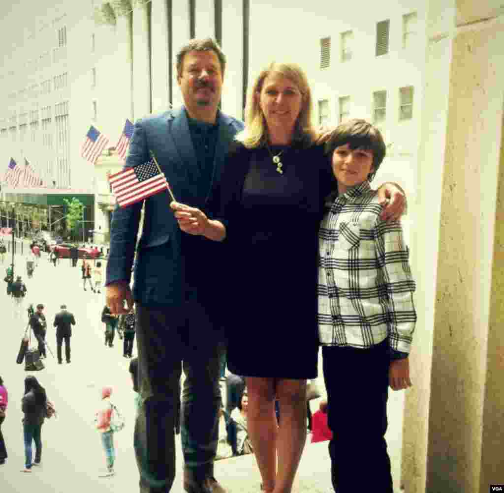 After the naturalization ceremony, Lesya Lysyj stands with her husband Bo and her son Lev on the steps of Federal Hall overlooking the New York Stock Exchange, May 22, 2014. (Adam Phillips/VOA)