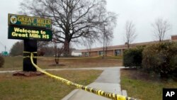 Crime scene tape is used around Great Mills High School, the scene of a shooting, March 20, 2018, in Great Mills. A student with a handgun shot two classmates inside the school before he was fatally wounded during a confrontation with a school resource of