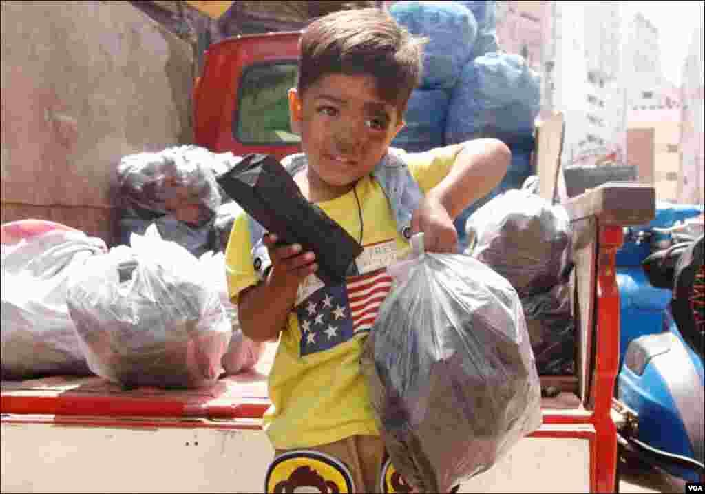 عید کیلئے بچوں کا جوش و خروش دیدنی، ایک بچہ کوئلہ کے ٹکڑوں کو اٹھائے ہوئے