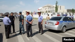 Investigators, Interior Ministry officers and members of security forces gather near the site of a bomb blast outside China's embassy in Bishkek, Kyrgyzstan, August 30, 2016.