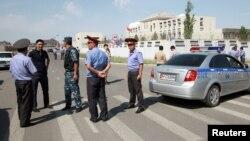 吉尔吉斯调查人员,内务部官员和警察在遇袭的中国驻吉尔吉斯斯坦大使馆附近(2016年8月30日)