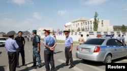 FILE - Investigators, interior ministry officers and members of security forces gather near the site of a bomb blast outside the Chinese Embassy in Bishkek, Kyrgyzstan, Aug. 30, 2016.