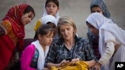 Dalam foto tertanggal 1/10/2011 ini, wartawan AP Kathy Gannon duduk dengan anak-anak perempuan di sebuah sekolah di Kandahar, Afghanistan.