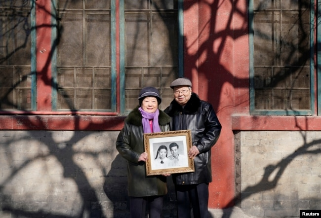 Huang Fusheng, right, 83, and his wife, Tang Lanfang, 80, pose with their wedding photo, taken in 1958, at Prince Fu Mansion built during Qing dynasty, where they worked together from 1965 to 1992, in central Beijing, China, Feb. 7, 2018.
