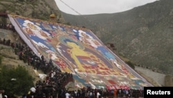 Tibetan Buddhists and tourists view a huge Thangka, a religious silk embroidery or painting displaying the Buddha portrait, during the Shoton Festival at Zhaibung Monastery in Lhasa, capital of southwest China's Tibet Autonomous Region, August 17, 2012.