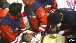 Petugas menyelamat mengangkat Ferhat Tokay, 13 tahun. Tokay telah berada di bawah reruntuhan bangunan akibat gempa di Ercis, Turki ini, selama lebih dari 100 jam.