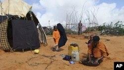图为一名来自南方的索马里女子8月4日在摩加迪沙一处临时难民营洗衣服