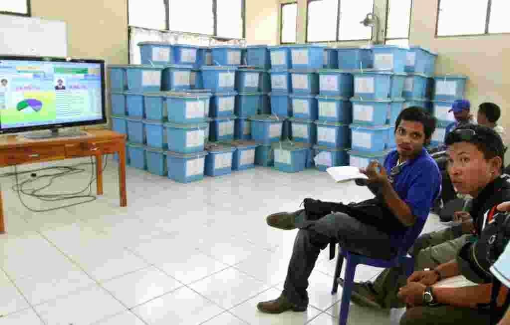 Warga menyaksikan hasil sementara pemilihan di televisi, Dili (18/3) (AP).