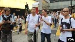 苹果日报老板黎智英(持伞)与大律师李柱铭参加13年七一游行(美国之音图片/海彦拍摄)