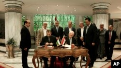 Senior Fatah official Azzam al-Ahmad, center right, and Hamas' representative, Saleh al-Arouri, center left, sign a reconciliation deal during a short ceremony at the Egyptian intelligence complex in Cairo, Egypt, Thursday, Oct. 12, 2017.