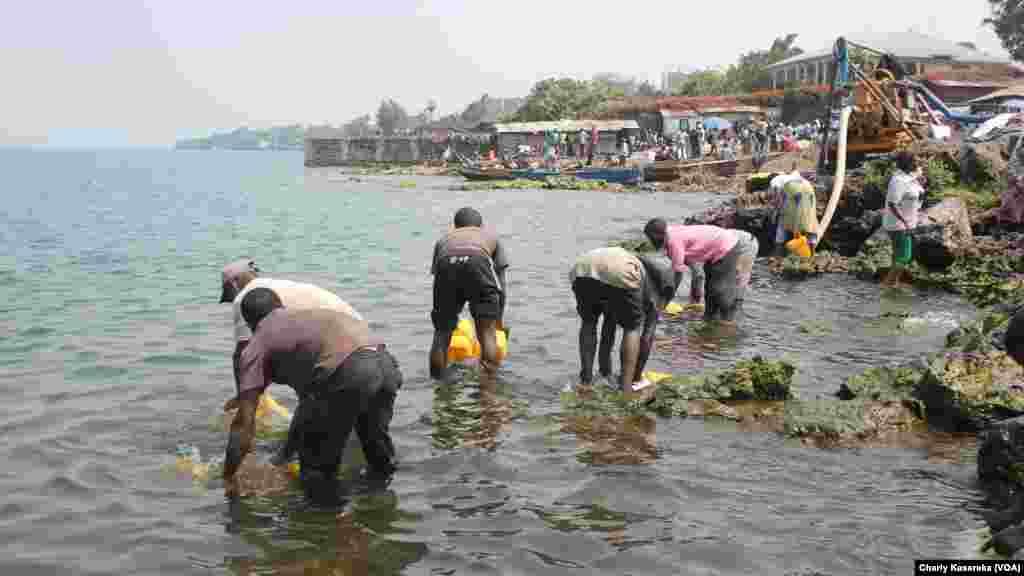 Des hommes et des femmes puisent l'eau du lac Kivu, à Goma, pour aller la vendre dans des quartiers non ou mal desservis par la Régie de distribution et traitement d'eau du Nord-kivu.