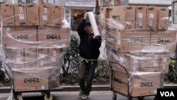 Seorang pekerja menggunakan plastik untuk mengamankan kotak-kotak produk Dell di pasar elektronik Nanjing, propinsi Jiangsu (7/3). Tiongkok melaporkan defisit perdagangan yang langka bulan Februari lalu