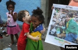 FILE - Cousins of Brazilian Judoka Rafaela Silva who won the gold medal in the 57 kg judo final, joke beside a newspaper with the picture of her next to the house where she was born at the City of God slum.