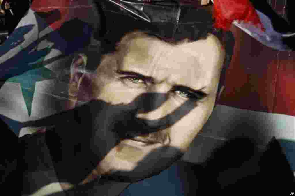 Shadows of Syrians are reflected on a giant poster showing President Bashar Assad, during a supporting rally in Damascus, Syria, Friday, Dec. 16, 2011. Syrian security forces opened fire on anti-government protesters after Friday prayers at several locati