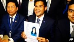 Leader of Thai Raksa Chart party Preecha Pholphongpanich, center, holds a picture of Princess Ubolratana at election commission of Thailand in Bangkok, Feb. 8, 2019. The political party has selected the princess as its nominee as the next prime minister.