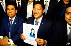 Leader of Thai Raksa Chart party Preecha Pholphongpanich, center, holds a picture of Princess Ubolratana at election commission of Thailand in Bangkok, Feb. 8, 2019.