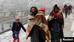 FILE - Syrian refugees brave the cold and snow as they walk to a metro station in Istanbul, February 11, 2015.