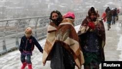 Người tị nạn Syria đi bộ trong thời tiết giá buốt ở Istanbul.
