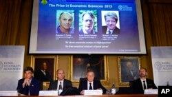 Akademi Sains Kerajaan Swedia Torsten Persson mengumumkan pemenang Nobel Ekonomi untuk tiga ekonom Amerika, yang ditayangkan di layar lebar (dari kiri: Eugene Fama, Lars Peter Hansen and Robert Shiller) dalam konferensi pers di Stockholm (14/10).