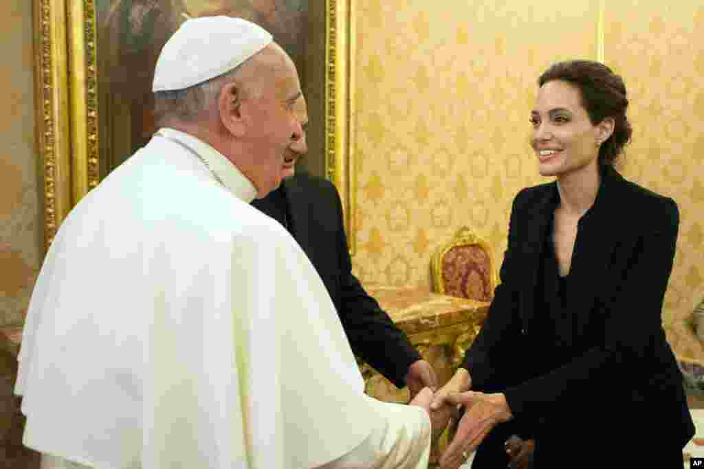Pope Francis greets Angelina Jolie in the Apostolic Palace at the Vatican after screening her film Unbroken to some Vatican officials and ambassadors.