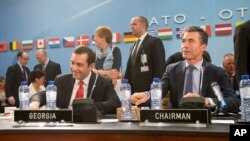 FILE - NATO Secretary-General Anders Fogh, right, and Georgian Defense Minister Irakli Alasania take their seat at a meeting of the NATO-Georgia Commission at NATO headquarters in Brussels, Belgium.