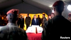 French President Francois Hollande (C) pays tribute near a flag-draped coffin bearing one of two French soldiers who was killed overnight, in Bangui, Dec. 10, 2013.
