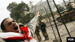 Un manifestante iracundo grita frente al palacio presidencial fuertemente custodiado por el ejército.