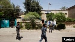Polisi berjaga di depan sebuah TPS di Baghdad (19/4). Seorang pembom bunuh diri meledakkan bomnya di sebuah kafe di ibukota Irak, Kamis (18/4), menewaskan 22 orang dan melukai puluhan lainnya menjelang pemilu propinsi yang akan diadakan akhir pekan ini.