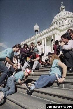 Sekelompok penyandang disabilitas yang dipimpin oleh Jennifer Keelan yang berusia 8 tahun, kiri, merangkak menaiki tangga US Capitol di Washington. (Foto: AP/Jeff Markowitz)
