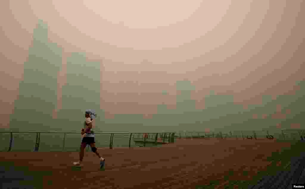 """A man jogs along the deserted Marina Promenade as the skyline of Singapore's central business district is covered in haze. Haze from fires in Indonesia could persist for weeks or longer. The smoke has driven air quality to """"hazardous"""" levels."""