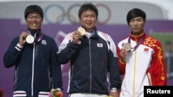 Silver medalist Japan's Takaharu Furukawa (L to R), gold medalist South Korea's Oh Jin Hyek and bronze medalist China's Dai Xiaoxiang pose during the victory ceremony for the men's individual archery event at the London 2012 Olympic Games at the Lord's C