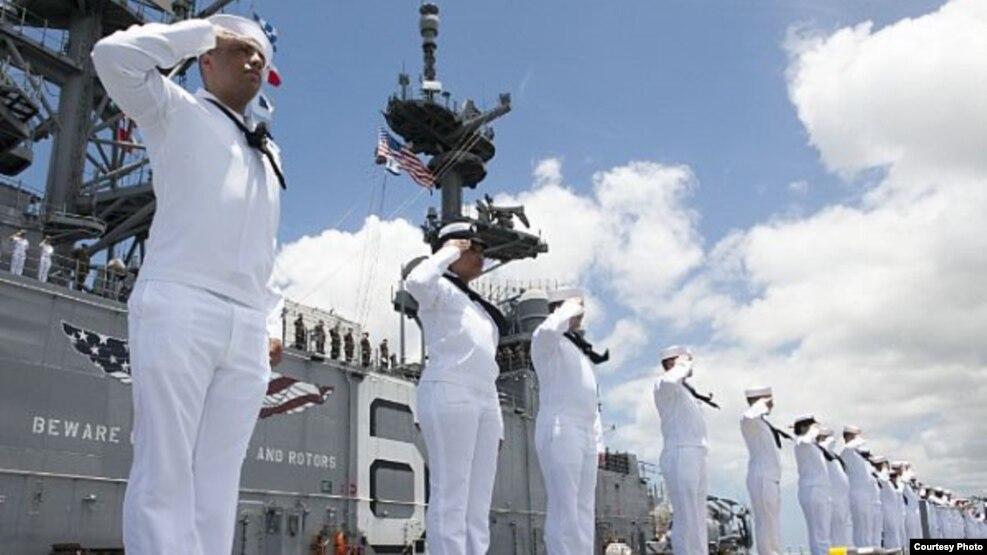 Marineros asignados al barco de asalto anfibio USS America saludan el Memorial USS Missouri y el Memorial USS Arizona a su paso por Pearl Harbor, Hawaii, el 30 de junio de 2016.