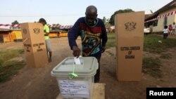 Seorang warga Ghana memasukkan surat suaranya ke kotak suara di salah satu TPS di Kibi, wilayah timur Ghana yang merupakan kubu calon presiden Nana Akufo-Addo dari oposisi Partai Patriotik Baru (NPP) (7/12).