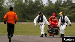 """Spasilačke ekipe prenose posmrtne ostatke jednog od putnika aviona """"Er Azije"""""""