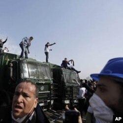 Des manifestants juchés sur des véhicules de forces de sécurité