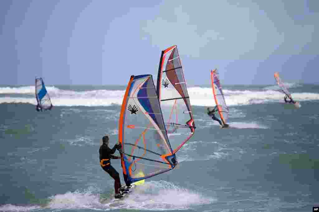 អ្នកជិះក្តារលើសមុទ្រ (wind surfers) ហាត់សមនៅលើទឹករលកនៃសមុទ្រមេឌីទែរ៉ាណេ នៅក្នុងក្រុង Haifa ប្រទេសអ៊ីស្រាអែល។