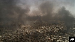 Fumées au dessus la vieille ville de Mossoul alors que les forces irakiennes poursuivent leurs combats contre les militants de l'État islamique à Mossoul, en Irak, le 3 juillet 2017. (AP / Felipe Dana)