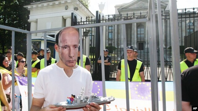 A man wears a mask depicting Russian President Vladimir Putin, during a protest against Russia's behavior in Ukraine in front of the Russian Embassy in Warsaw, July 27, 2014.