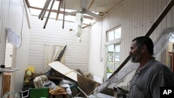 Rudy Luguna surveys the damage in his house he owns with his brother after the roof was ripped off in Tully, Australia, February 3, 2011